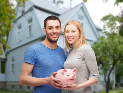 smiling couple holding piggy bank over house